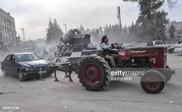 A Turkishbacked Syrian Arab fighter tows a looted vehicle with a tractor after seizing control of the northwestern Syrian city of Afrin from the...