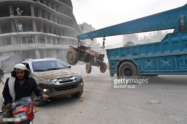 Turkishbacked Syrian Arab fighters drive a lorry carrying a looted tractor after seizing control of the northwestern Syrian city of Afrin from the...