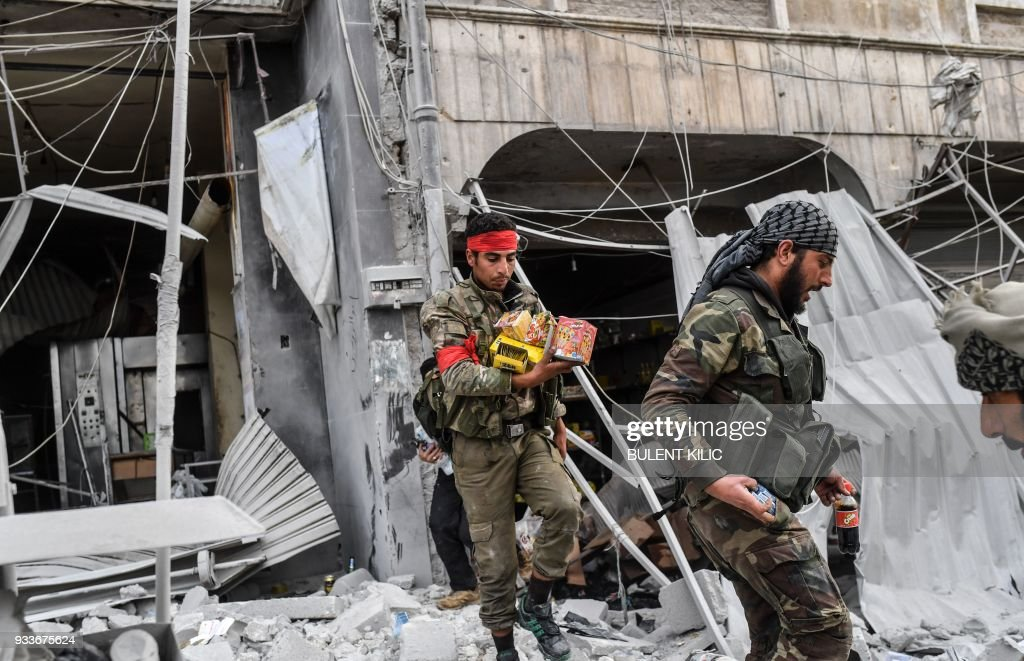 Turkish-backed Syrian Arab fighters loot shops after seizing control of the northwestern Syrian city of Afrin from the Kurdish People's Protection Units (YPG) on March 18, 2018. In a major victory for Ankara's two-month operation against the Kurdish People's Protection Units (YPG) in northern Syria, Turkish-led forces pushed into Afrin apparently unopposed, taking up positions across the city. /
