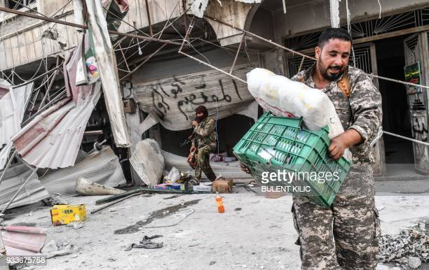 TOPSHOT Turkishbacked Syrian Arab fighters loot shops after seizing control of the northwestern Syrian city of Afrin from the Kurdish People's...