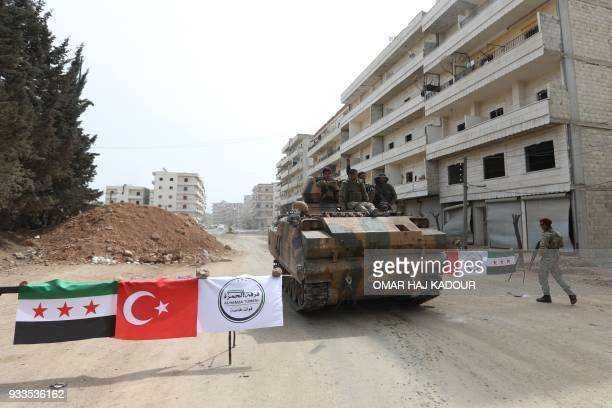 TOPSHOT Turkishbacked Syrian Arab fighters man a checkpoint in the Kurdishmajority city of Afrin in northwestern Syria after seizing control of it...