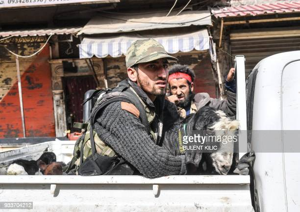 TOPSHOT Turkishbacked Syrian Arab fighters ride the back of a pickup with looted livestock after seizing control of the northwestern Syrian city of...