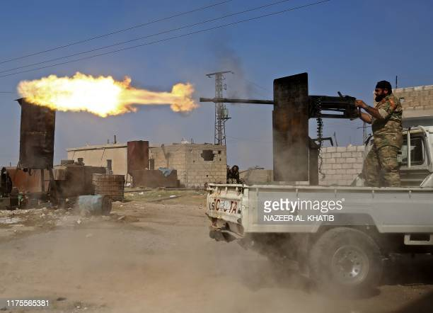 Turkish-backed Syrian fighter fires during clashes in the border town of Ras al-Ain on October 13 as Turkey and its allies continue their assault on...