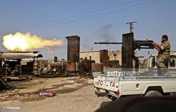 A Turkishbacked Syrian fighter fires during clashes in the border town of Ras alAin on October 13 as Turkey and its allies continue their assault on...