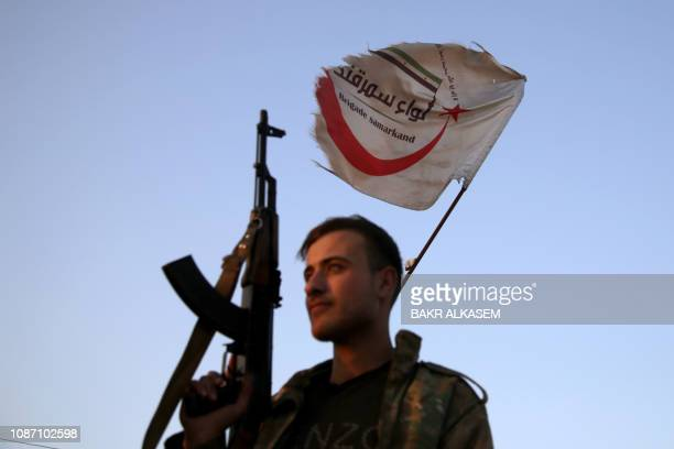 Turkishbacked Syrian fighter from the Samarkand Brigade holds up an assault rifle as he stands at a position along the frontline with SDF forces near...