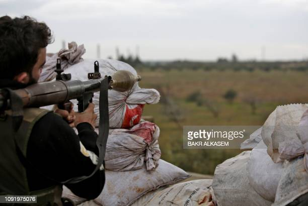 A Turkishbacked Syrian fighter holds a rocketpropelled grenade launcher as he keeps position near the town of Tal Hajar in Syria's northern Aleppo...