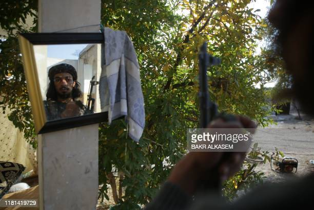 Turkish-backed Syrian fighter looks in a mirror at a position held in the village of al-Yalishli in the countryside of Manbij, a strategic...