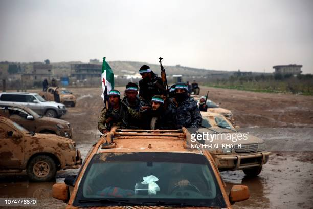 TOPSHOT Turkishbacked Syrian fighters are pictured in the back of their trucks as they leave their barracks in the rebelheld border town of Jarabulus...
