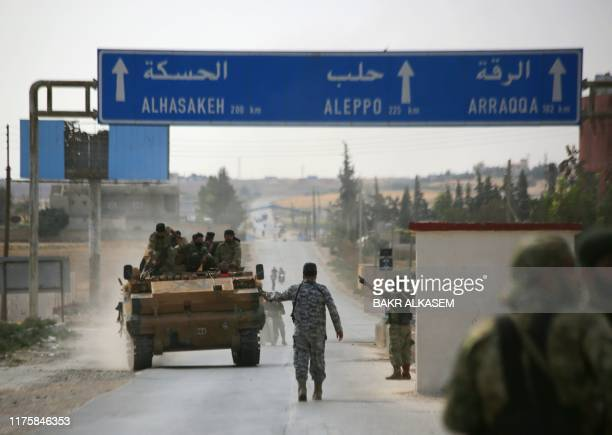 Turkishbacked Syrian fighters are pictured in the town of Ayn alArus south of the border town of Tal Abyad on October 14 as Turkey and its allies...