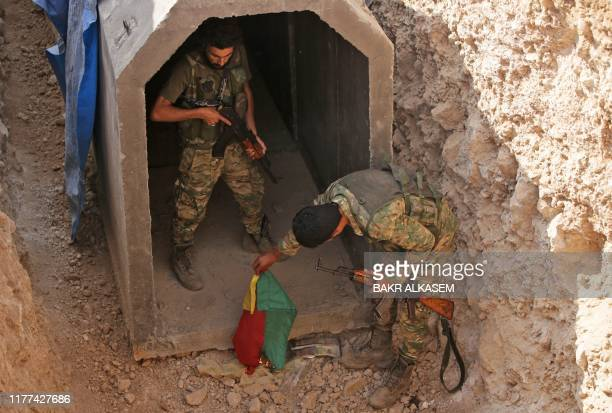 TOPSHOT Turkishbacked Syrian fighters burn a flag at the entrance of a tunnel said to have been built by Kurdish fighters in the Syrian border town...