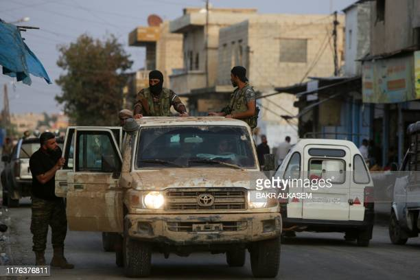 Turkishbacked Syrian fighters drive down a street in the Syrian border town of Tal Abyad on October 17 as Turkey and its allies continue their...