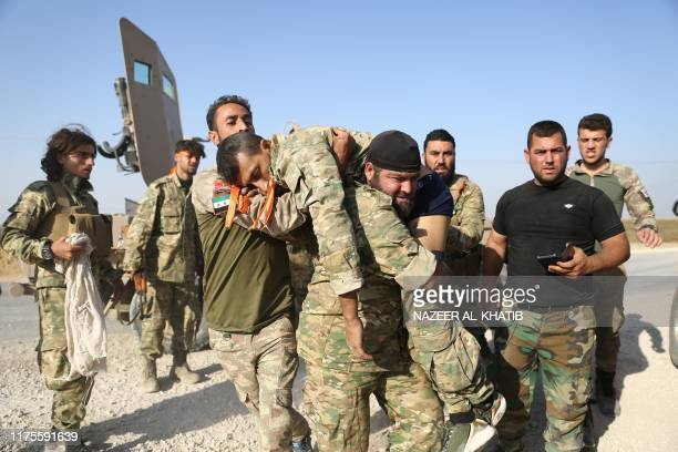 TOPSHOT Turkishbacked Syrian fighters evacuate a wounded comrade near the border town of Ras alAin on October 13 as Turkey and its allies continue...