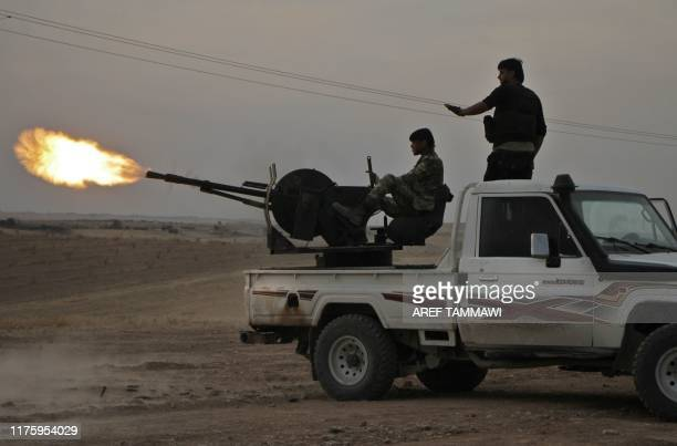 Turkishbacked Syrian fighters fire a truck mounted heavy gun near the town of Tukhar north of Syria's northern city of Manbij on October 14 as Turkey...