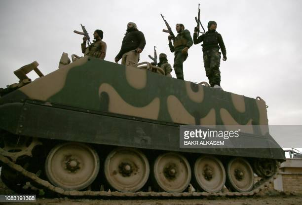 Turkish-backed Syrian fighters participate in a training manuever using an armoured vehicle provided by the Turkish army, near the town of Tal Hajar...