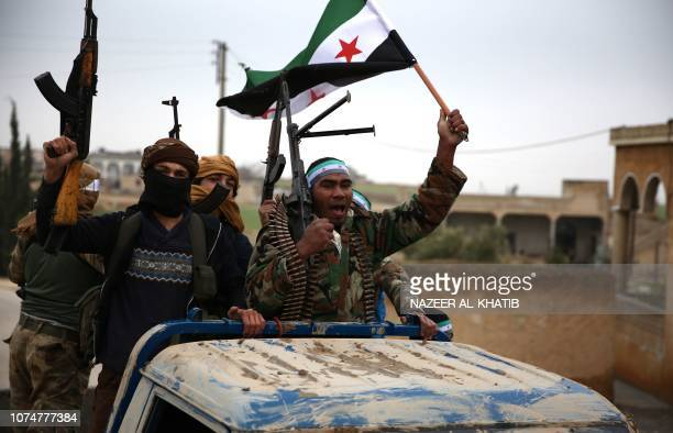 TOPSHOT Turkishbacked Syrian fighters raise the opposition flag as they arrive in the border rebelheld town of Qirata after leaving their barracks in...