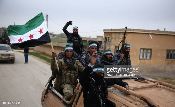 Turkishbacked Syrian fighters raise the opposition flag as they arrive in the border rebelheld town of Qirata after leaving their barracks in the...