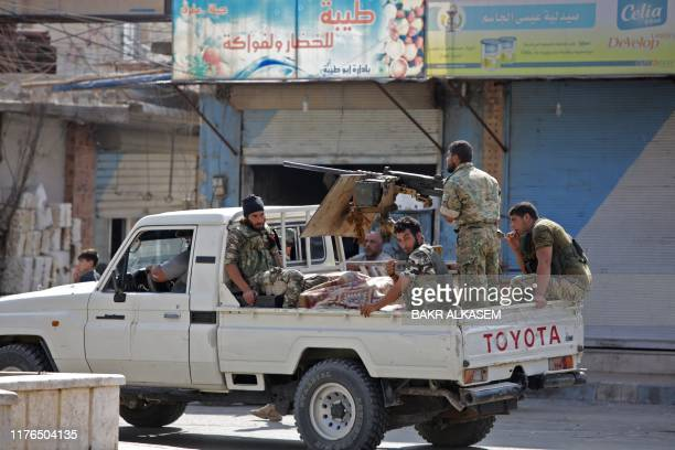 Turkishbacked Syrian fighters ride in the back of a pick up truck in the Syrian border town of Tal Abyad on October 18 after a ceasefire was...