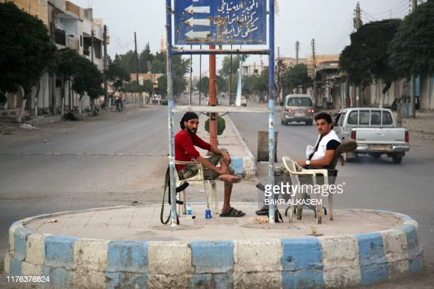 TOPSHOT Turkishbacked Syrian fighters sit in the middle of a roundabout in the Syrian border town of Tal Abyad on October 17 as Turkey and its allies...