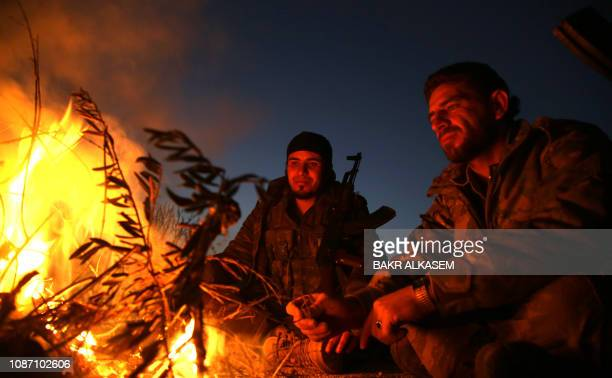 Turkish-backed Syrian fighters sit with their firearms around a campfire at a position along the frontline with SDF forces near the village of...