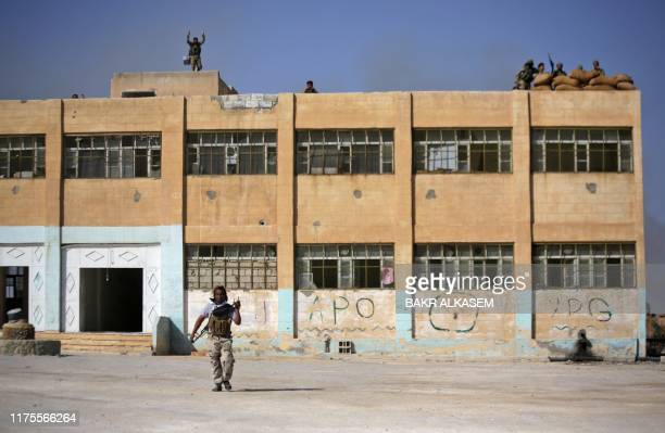 Turkish-backed Syrian fighters take position on top of a building in the southwestern neighbourhoods of the border town of Tal Abyad on October 13,...