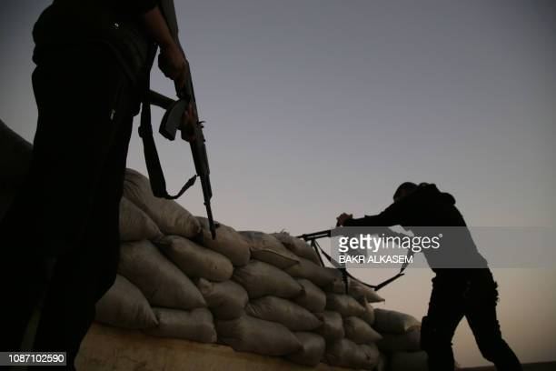 TOPSHOT Turkishbacked Syrian fighters take up an armed position with sandbags along the frontline with SDF forces near the village of Kiridiyah about...