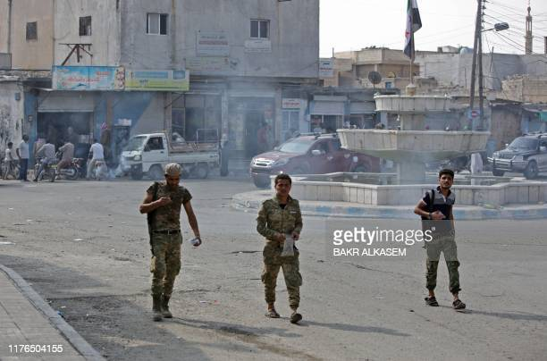 Turkish-backed Syrian fighters walk in the Syrian border town of Tal Abyad on October 18 after a ceasefire was announced the previous day. - Deadly...