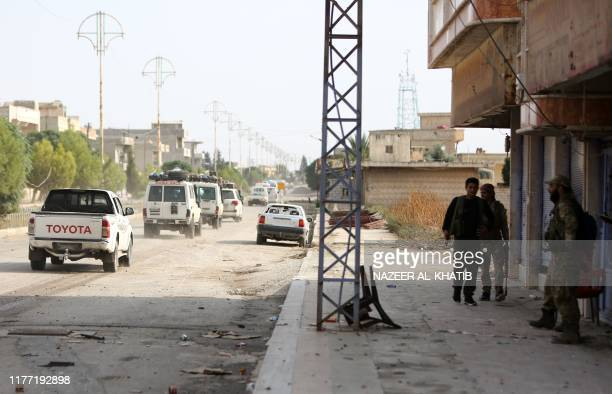 Turkishbacked Syrian fighters watch a convoy of ambulances and other vehicles evacuating fighters and injured members of the Kurdishled Syrian...
