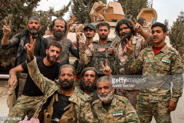 "Turkish-backed Syrian fighters, with one of them wearing the emblem of the Turkish far-right ""Grey Wolves"" movement, pose for a group picture while..."