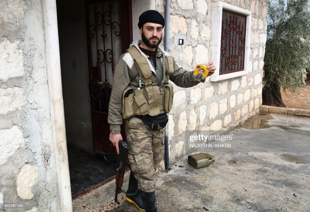 A Turkish-backed Syrian opposition fighter holds a picture of a People's Protection Units (YPG) fighter as they battle for control of the village of al-Bayyah northeast of the town of Afrin near the border with Turkey on February 21, 2018. / AFP PHOTO / Nazeer al-Khatib