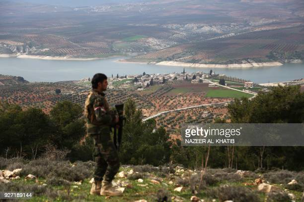Turkishbacked Syrian opposition fighter walks along a ridge overlooking Lake Maydanki north of the Syrian city of Afrin after they took control of...