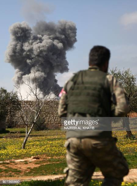 Turkishbacked Syrian opposition fighters are seen in the village of Jamanli northeast of the Syrian city of Afrin on March 3 as smoke billows in the...
