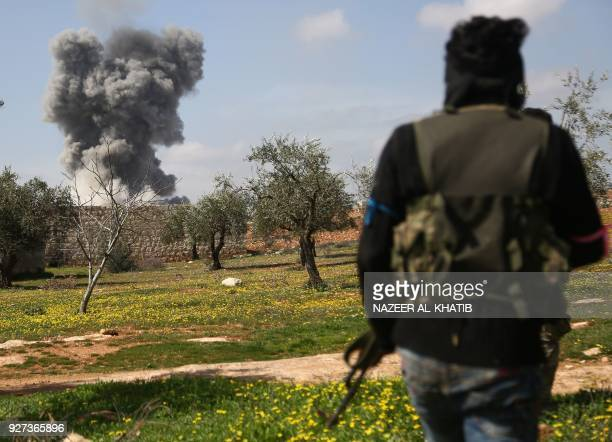 TOPSHOT Turkishbacked Syrian opposition fighters are seen in the village of Jamanli northeast of the Syrian city of Afrin on March 3 as smoke billows...