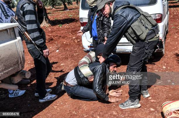 Turkishbacked Syrian opposition fighters attempt to detain a young man as a woman tries to stop them ahead of crossing to the Turkishbacked Syrian...