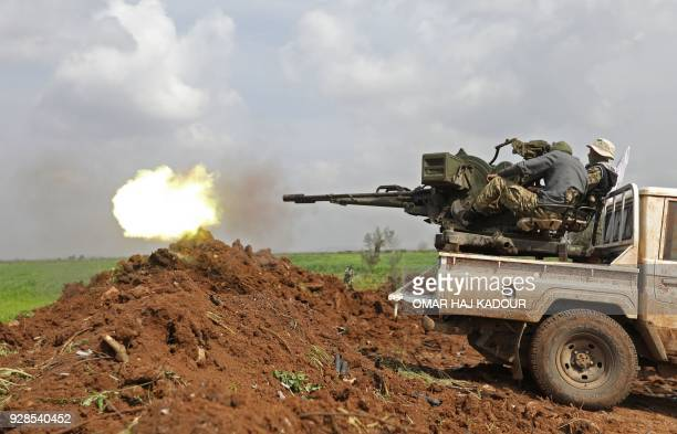 TOPSHOT Turkishbacked Syrian opposition fighters fire an antiaircraft gun during battles with Kurdish fighters on the outskirts of the town of...