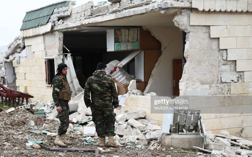 Turkish-backed Syrian opposition fighters looks at a damaged house as they battle for control of the village of al-Bayyah northeast of the town of Afrin near the border with Turkey on February 21, 2018. / AFP PHOTO / Nazeer al-Khatib