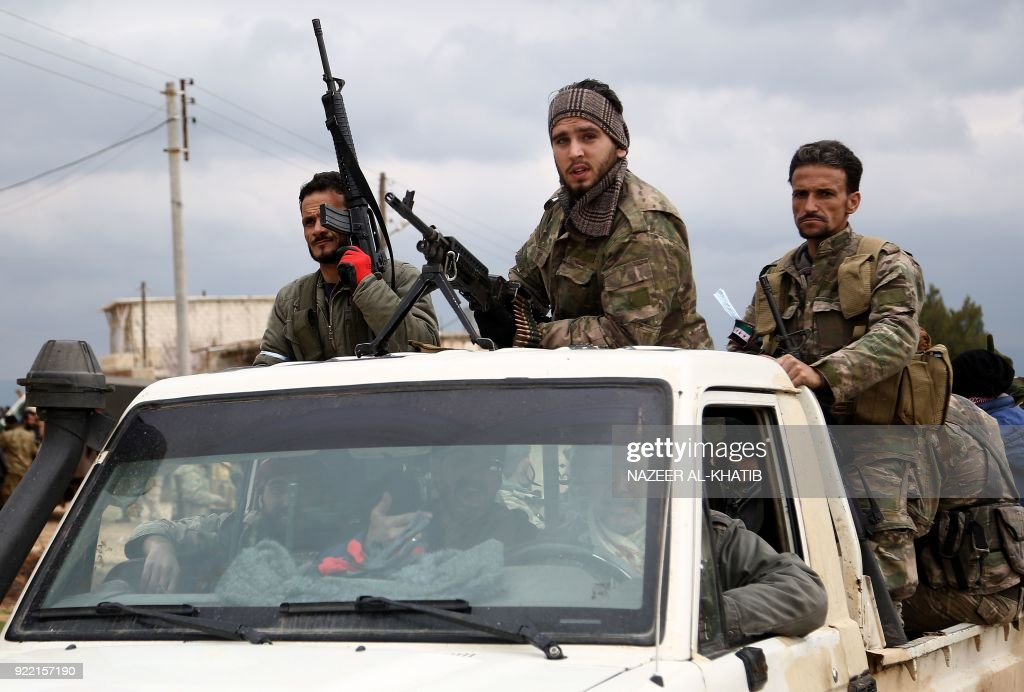 Turkish-backed Syrian opposition fighters move in a vehicle as they battle for control of the village of al-Bayyah northeast of the town of Afrin near the border with Turkey on February 21, 2018. / AFP PHOTO / Nazeer al-Khatib