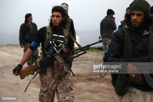 Turkishbacked Syrian opposition fighters walk during the battle to take over the town of Sharran which is controlled by Kurdish People's Protection...
