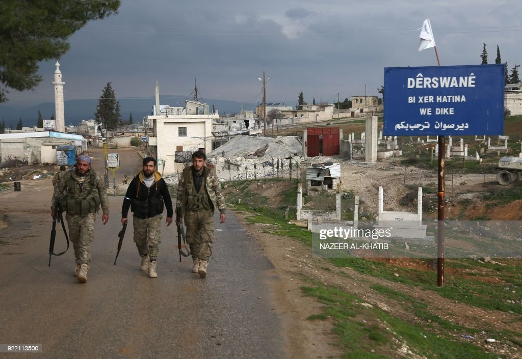 Turkish-backed Syrian opposition fighters walk in the village of Deir Sawwan, northeast of the town of Afrin near the border with Turkey after they took control of the village on February 21, 2018. / AFP PHOTO / Nazeer al-Khatib