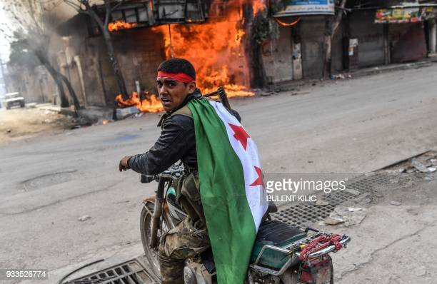Turkishbacked Syrian rebel drives past a burning shop in the city of Afrin in northern Syria on March 18 2018 Turkish forces and their rebel allies...