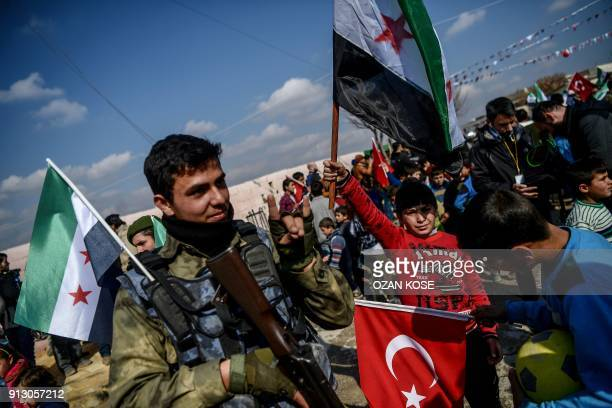 Turkishbacked Syrian rebel fighter gestures as he holds Free Syrian Army flag next to Syrian children holding Turkish national flag and a Free Syrian...