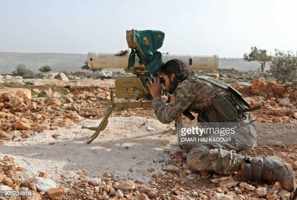 A Turkishbacked Syrian rebel fighter looks through the scope of a rocket launcher at a monitoring point near the Syrian village of Qilah in the...