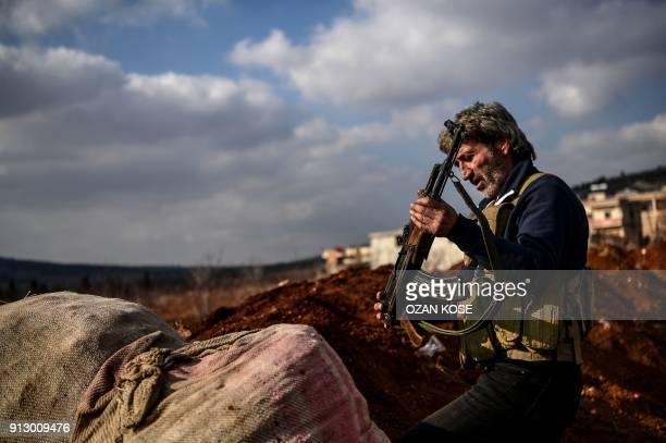 Turkish-backed Syrian rebel fighter stands guard at a checkpoint in the Syrian town of Azaz on a road leading to Afrin, on February 1, 2018. - Turkey...