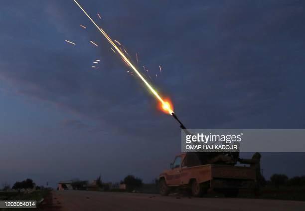 TOPSHOT Turkishbacked Syrian rebel fighters fire their antiaircraft gun in the town of Sarmin about eight kilometres southeast of the city of Idlib...