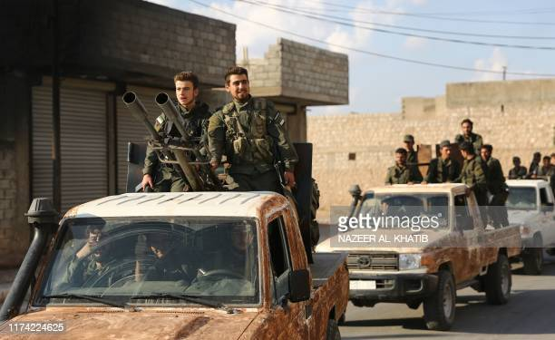 Turkishbacked Syrian rebel fighters gather near the SyrianTurkish border north of Aleppo on October 7 2019 US forces in northern Syria started...