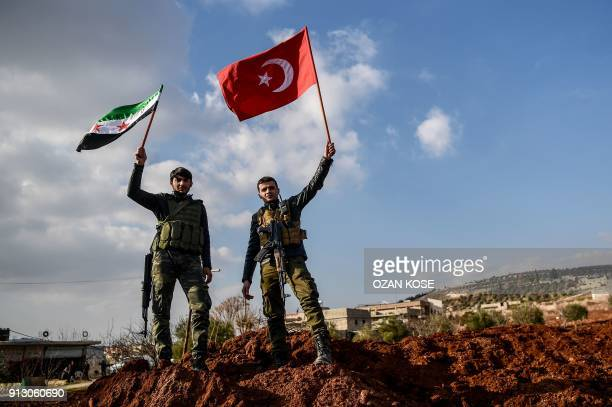 Turkishbacked Syrian rebel fighters hold Turkish national flag and Free Syrian Army flags at a checkpoint in the Syrian town of Azaz on a road...