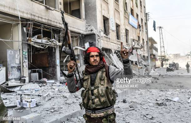 Turkishbacked Syrian rebel gestures as they gather in the city of Afrin in northern Syria on March 18 2018 Turkish forces and their rebel allies were...