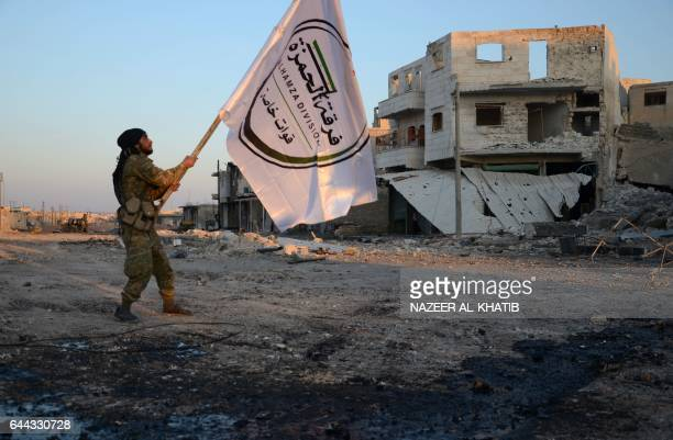 A Turkishbacked Syrian rebel holds the flag of his division in the northwestern border town of alBab on February 23 2017 after they fully captured...