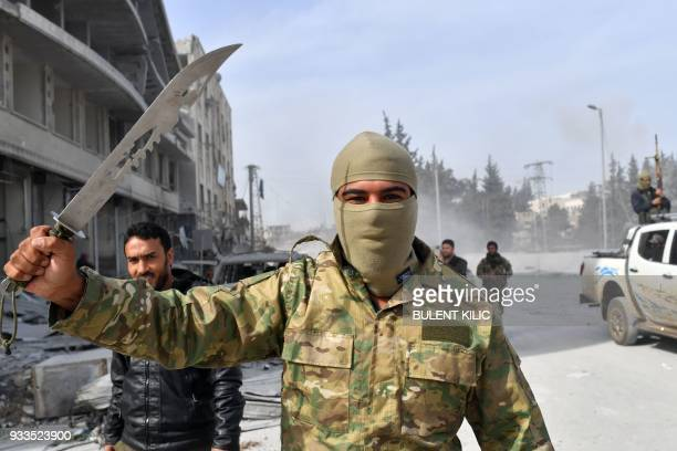 Turkishbacked Syrian rebel raises a dagger as they gather in the city of Afrin in northern Syria on March 18 2018 Turkish forces and their rebel...