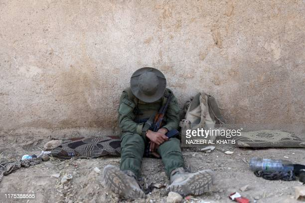Turkishbacked Syrian rebel rests as they gather near the border town of Ras alAin on October 12 as Turkey and its allies continued their assault on...