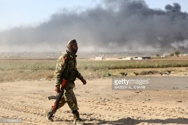 A Turkishbacked Syrian rebel walks in a field outside the border town of Ras alAin on October 12 during their assault on Kurdishheld border towns in...